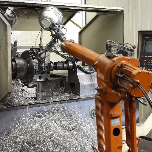 Roboterarm entnimmt einen PAR-64 Lampendeckel aus einer Drehbank